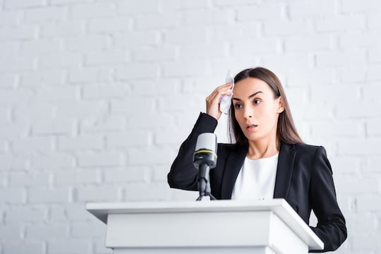 worried lecturer, suffering from glossophobia, holding napkin near forehead while standing on podium tribune